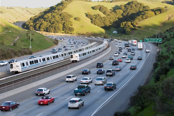 Surrounded by cars, BART travels between a highway in the East Bay.