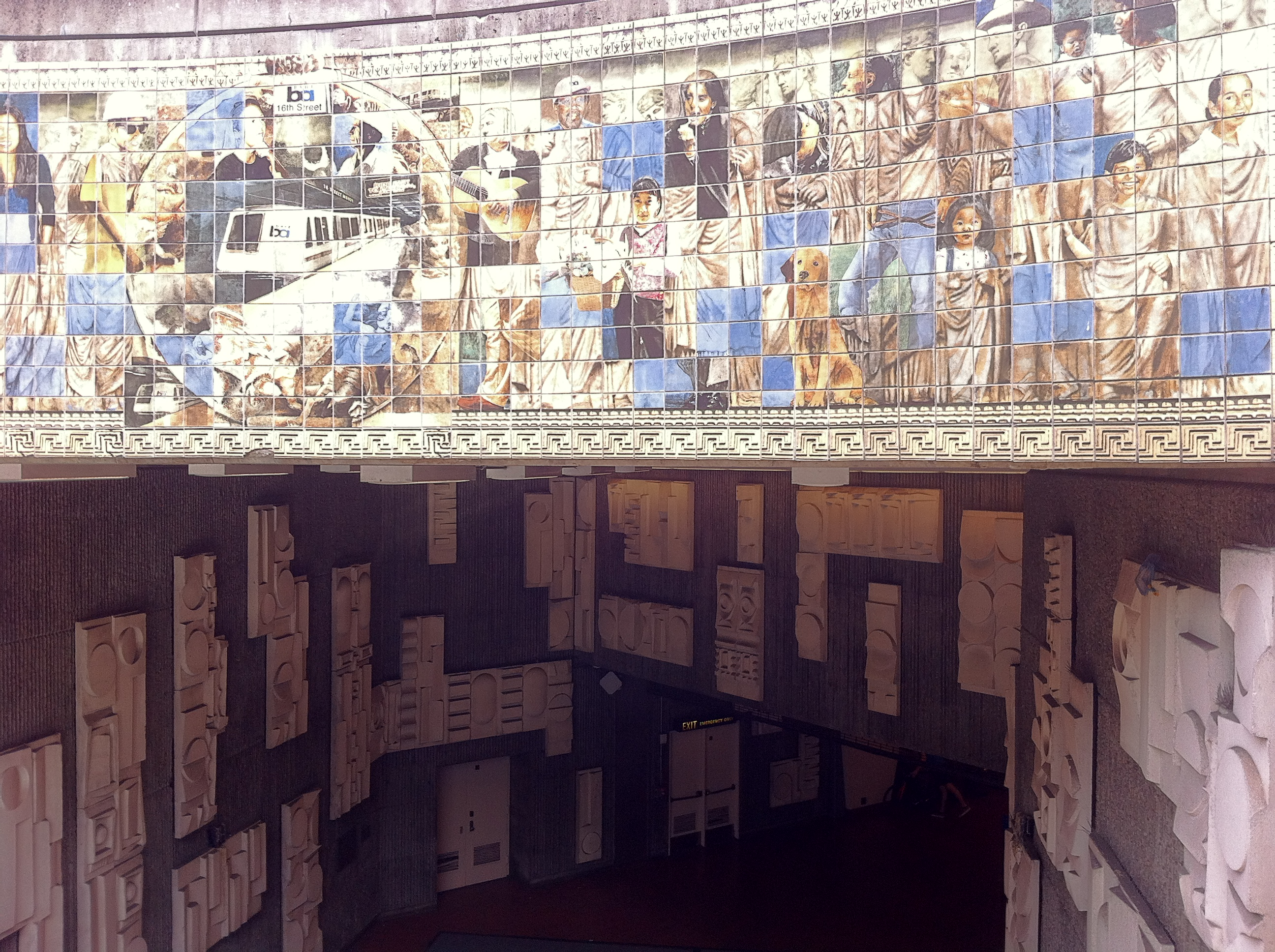 Image showing tile mural art, and concrete relief art at 16th St Mission BART station. Tile mural is titled Future Roads by Daniel Galvez and Jos Sances. The concrete low relief artwork is by William Mitchell