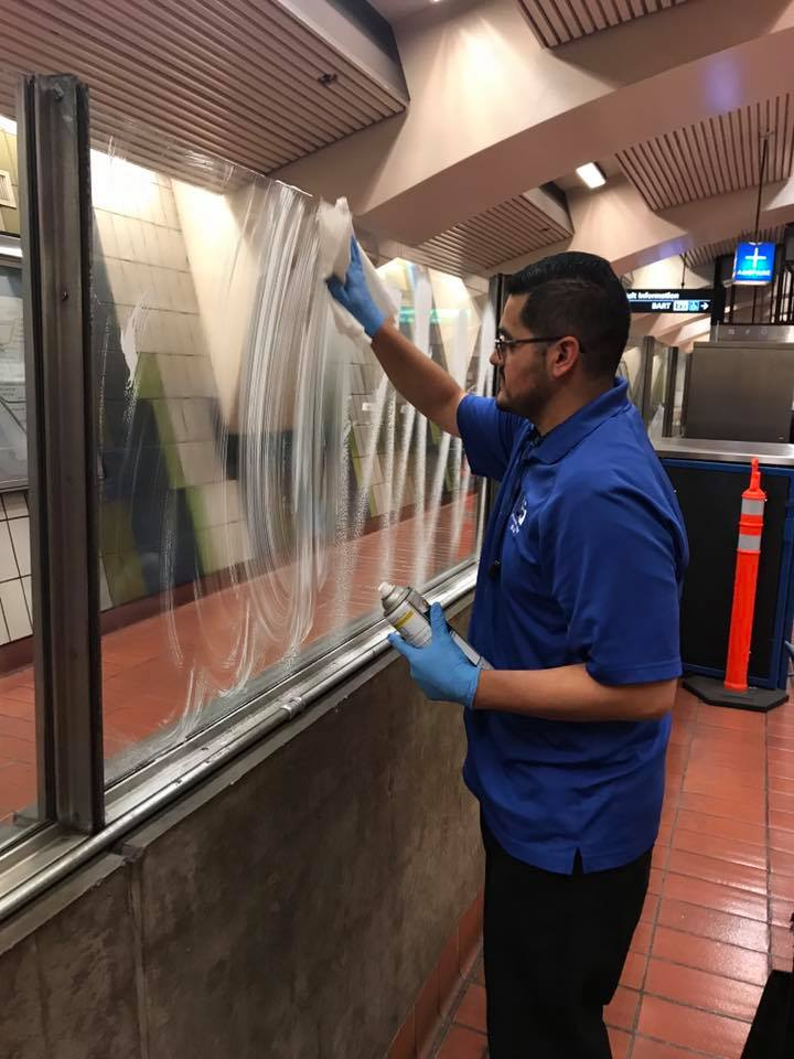 Jorge wiping down window panes at 16th St Mission Station