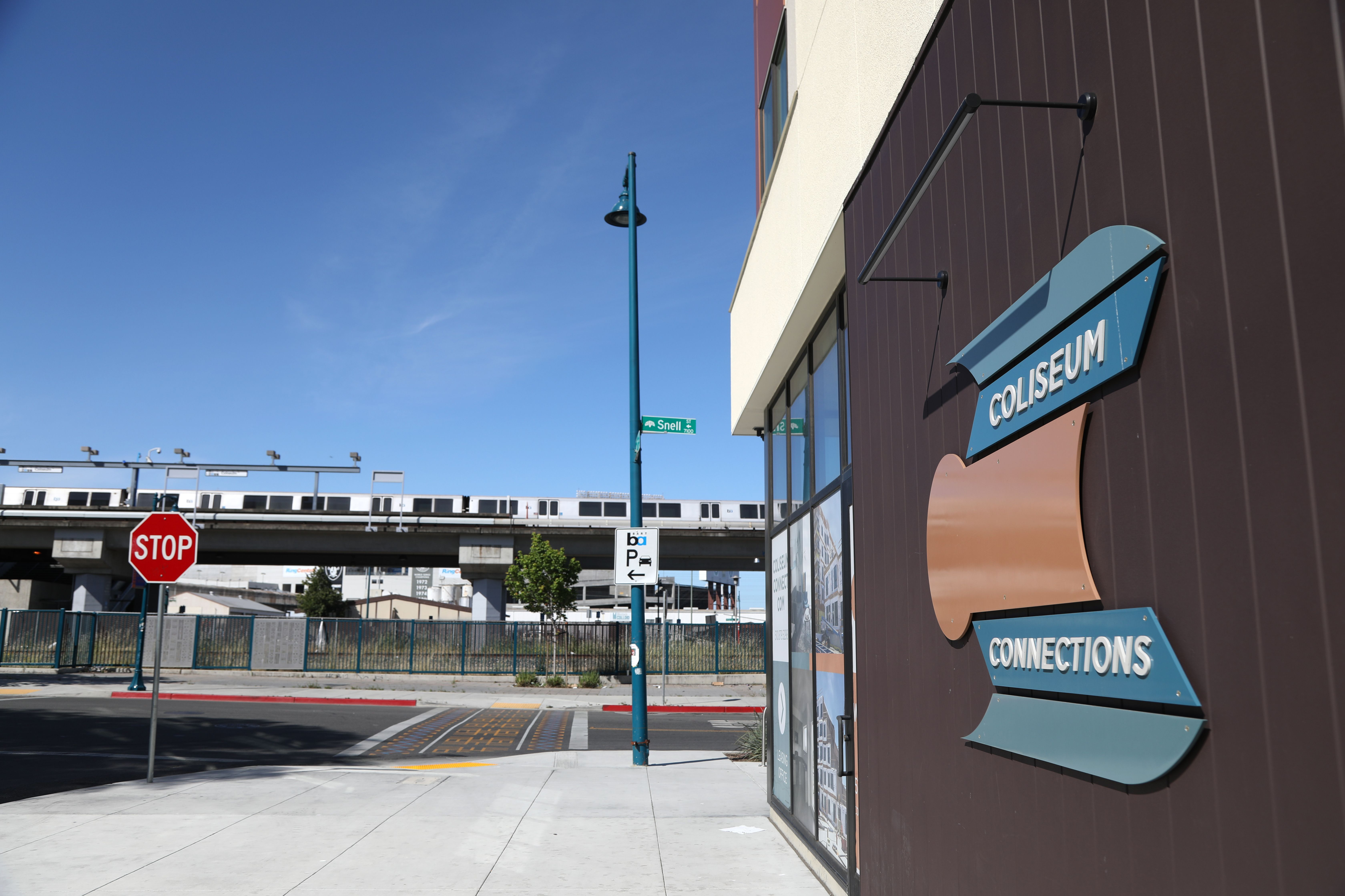 Exterior view of Coliseum Connections building with BART train in the background