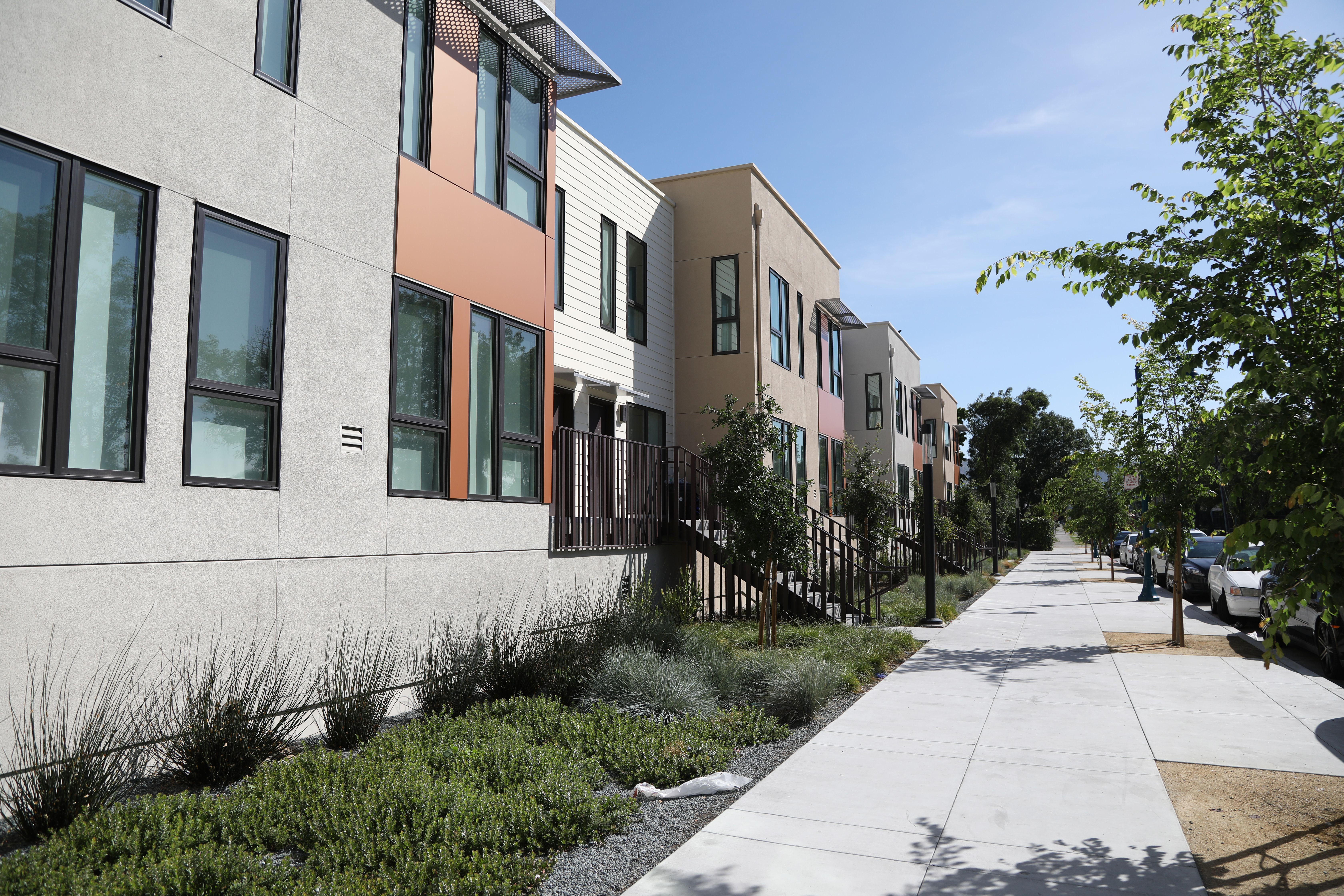 Wide sidewalks and environmentally friendly landscaping surround the apartment units