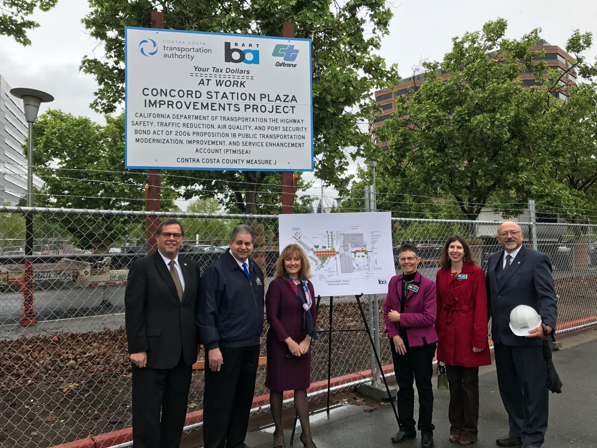 directors and local officials standing in front of construction sign