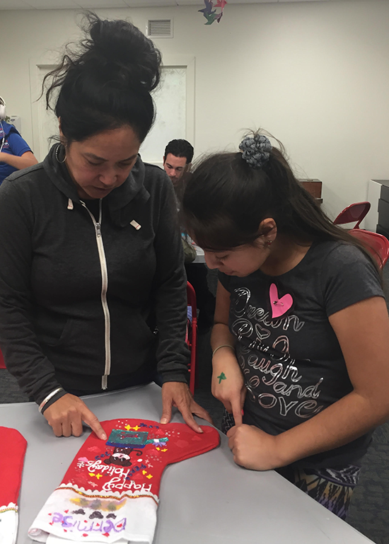 Denise Obrero helps a child making a stocking