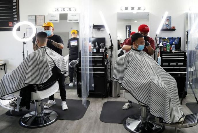Barbers Mark DeGuzman, foreground, and Romel Diaz at their Hayward shop