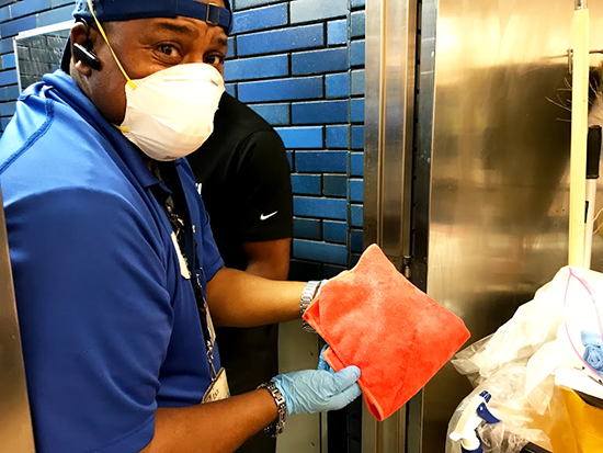 Milton Bradford wears Personal Protective Equipment while cleaning on a field trip to a station.