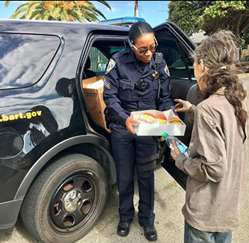 Sgt. Carter gives food and water to a homeless woman