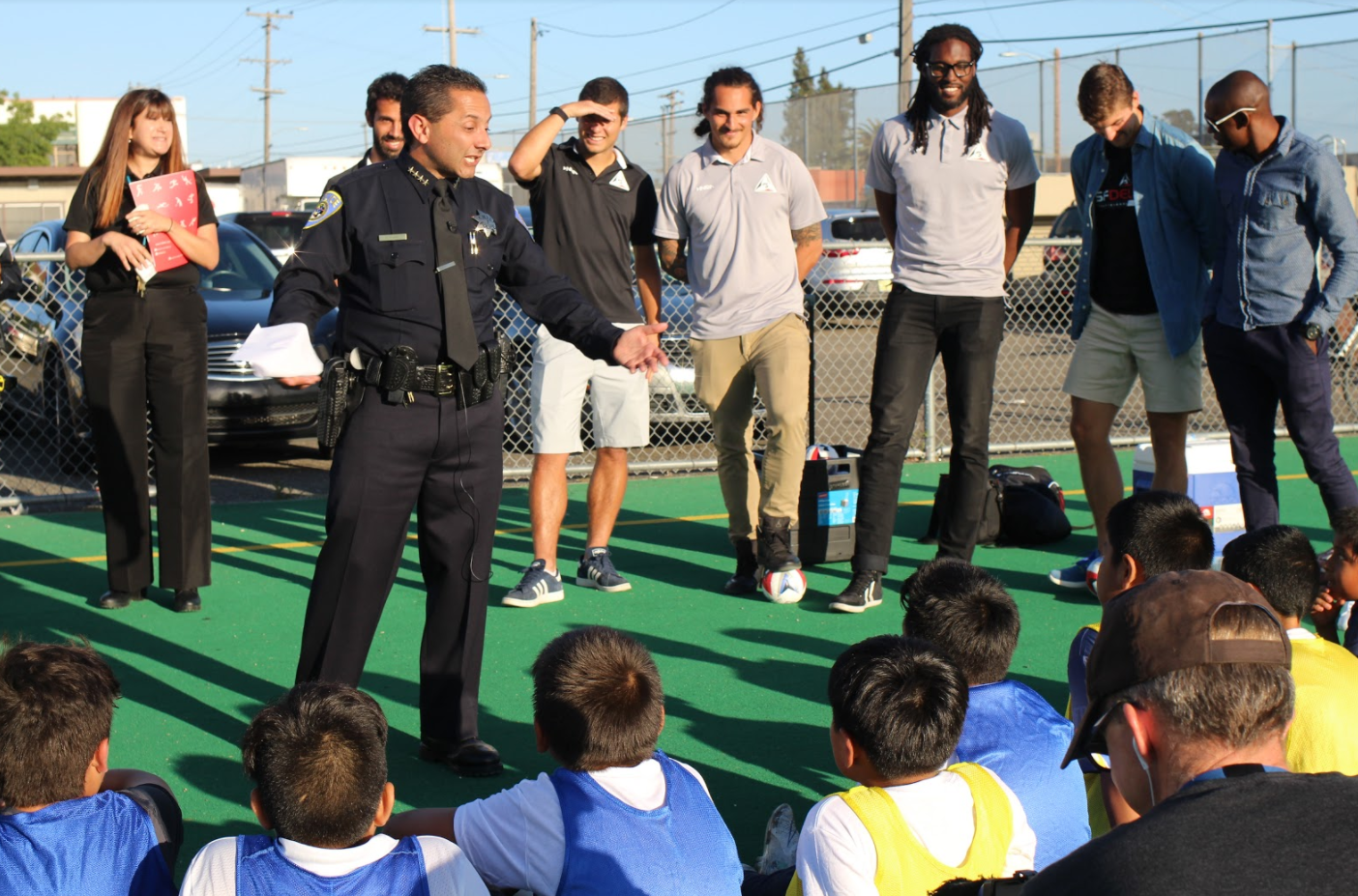 BART Police Chief Carlos Rojas visits with Leopards players at a practice