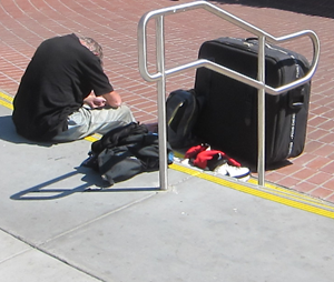 man waits with belongings