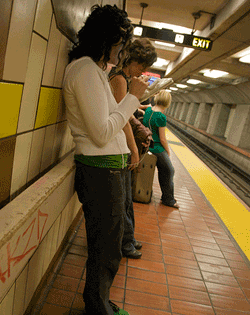 woman in BART station using iPhone