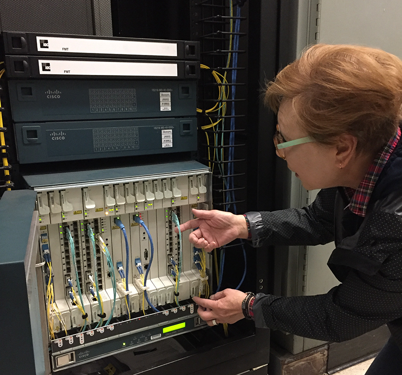 Senior Computer Systems Engineer Julia Quittman inspects part of the Unified Optical Network