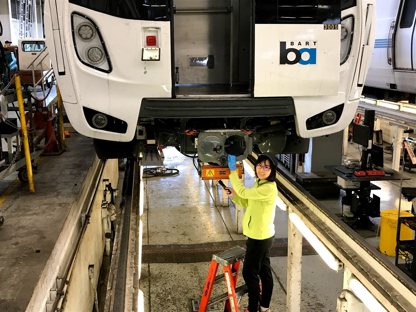 Rosa Sung in the pit under a Fleet of the Future train at the Hayward Maintenance Shop