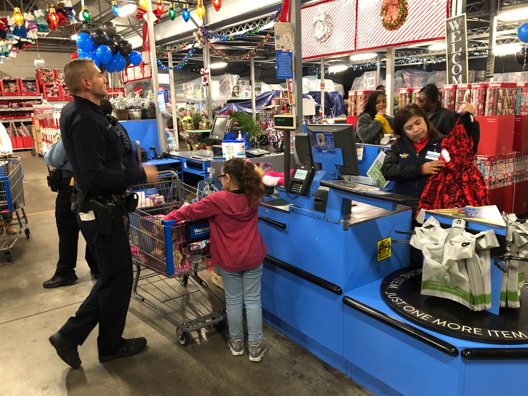 Child and cop unloading their shopping cart for cashier