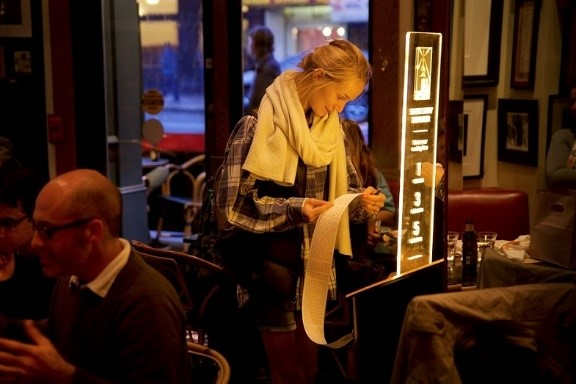 A customer at Café Zoetrope uses a Short Story Dispenser; image by Olivier Alexandre - Short Edition