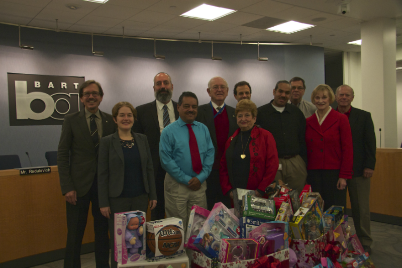 BART board of directors behind a pile of toys