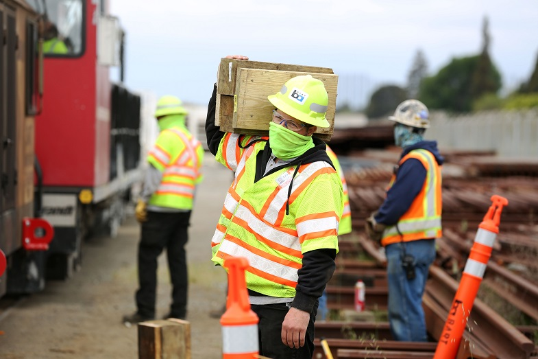 A worker carries wood blocks that are used in positioning a rail grinder. Contractor VSCE Inc. was on site at the Hayward mainte