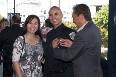 Officer Phi Le at his graduation with his parents.