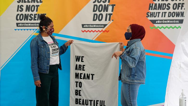 """Organizers pose for a photo holding banner """"We Are Meant to Be Beautiful"""" at Not One More Girl's Art Activation event."""