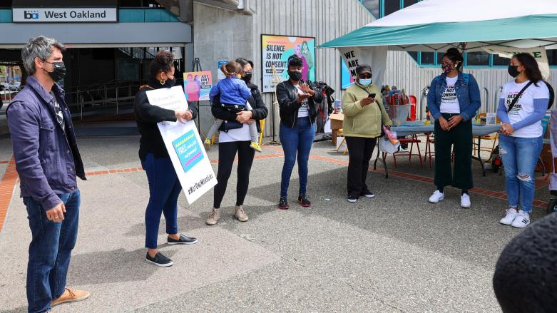 Organizers and participants huddle around at Not One More Girl's Art Activation event at West Oakland BART Station on April 24.