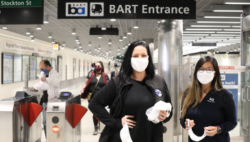 2 station agents in masks greeting riders